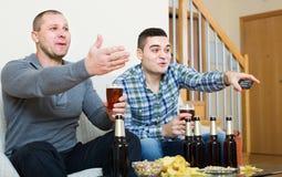 Δύο άτομα που προσέχουν το ποδόσφαιρο με την μπύρα εσωτερική Στοκ φωτογραφία με δικαίωμα ελεύθερης χρήσης