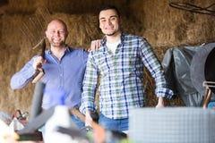 Δύο αγρότες που εργάζονται στη σιταποθήκη Στοκ εικόνα με δικαίωμα ελεύθερης χρήσης