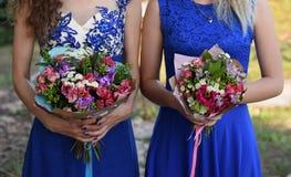 δύο γυναίκες που κρατούν τις ανθοδέσμες Στοκ εικόνα με δικαίωμα ελεύθερης χρήσης