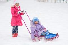Δύο κορίτσια οδηγούν το ένα το άλλο σε ένα έλκηθρο Στοκ Φωτογραφίες