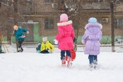 Δύο κορίτσια τρέχουν στα άλλα παιδιά για να οδηγήσουν σε έναν παγωμένο λόφο στο ναυπηγείο Στοκ φωτογραφία με δικαίωμα ελεύθερης χρήσης