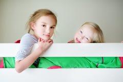 Δύο μικρές αδελφές που γύρω, που παίζουν και που έχουν η διασκέδαση στο δίδυμο κρεβάτι κουκετών Στοκ εικόνες με δικαίωμα ελεύθερης χρήσης