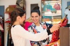 Δύο νέα κορίτσια στη μπουτίκ που επιλέγουν το φόρεμα Στοκ φωτογραφία με δικαίωμα ελεύθερης χρήσης