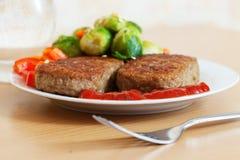 Δύο τηγανισμένα cutlets με τα λαχανικά Στοκ Εικόνες
