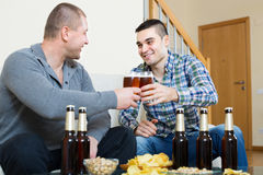 Δύο φίλοι που πίνουν την μπύρα στο σπίτι Στοκ Εικόνες