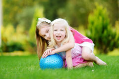 Δύο χαριτωμένες μικρές αδελφές που έχουν τη διασκέδαση μαζί στη χλόη Στοκ εικόνες με δικαίωμα ελεύθερης χρήσης