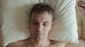 Ύπνοι ατόμων στο κρεβάτι με έναν ανήσυχο ύπνο Αισθητά ανοίγει τα μάτια του, εξετάζει τη κάμερα και κραυγάζει στον τρόμο φιλμ μικρού μήκους