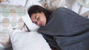 Ύπνοι γυναικών ήσυχα στο κρεβάτι της, που τυλίγεται στα καλύμματα κατά τη διάρκεια των ονείρων, σε αργή κίνηση φιλμ μικρού μήκους