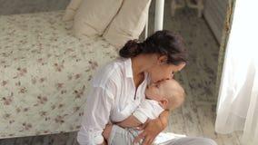 Ύπνοι μικροί νεογέννητοι μωρών στα όπλα της μητέρας του στην κρεβατοκάμαρα φιλμ μικρού μήκους