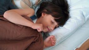 Ύπνοι μικρών κοριτσιών γλυκά στο κρεβάτι, τα ίχνη επάνω και τα τεντώματα, σε αργή κίνηση φιλμ μικρού μήκους