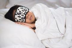 Ύπνος αγοριών στο άσπρα μαξιλάρι και τα σεντόνια με τη μάσκα ύπνου Στοκ φωτογραφία με δικαίωμα ελεύθερης χρήσης