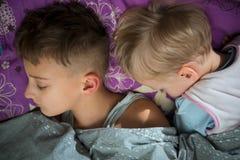 Ύπνος αδελφών δύο αγοριών στο ίδιο κρεβάτι Στοκ Εικόνες
