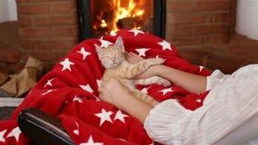 Ύπνος γατακιών στην περιτύλιξη γυναικών μπροστά από την εστία απόθεμα βίντεο