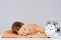 Ύπνος γυναικών παράλληλα με ένα ξυπνητήρι Στοκ εικόνα με δικαίωμα ελεύθερης χρήσης