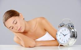 Ύπνος γυναικών παράλληλα με ένα ξυπνητήρι Στοκ εικόνες με δικαίωμα ελεύθερης χρήσης