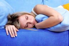 Ύπνος γυναικών στα μαξιλάρια στον καναπέ Στοκ εικόνα με δικαίωμα ελεύθερης χρήσης