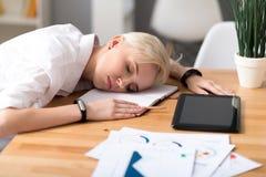 Ύπνος γυναικών στον πίνακα εργαζόμενος Στοκ εικόνα με δικαίωμα ελεύθερης χρήσης