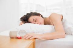 Ύπνος γυναικών στο κρεβάτι από το μπουκάλι των χαπιών στον πίνακα στοκ φωτογραφίες