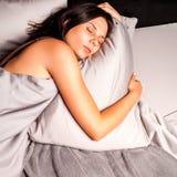 Ύπνος γυναικών στο κρεβάτι σε ένα σκοτεινό υπόβαθρο Στοκ φωτογραφία με δικαίωμα ελεύθερης χρήσης