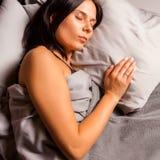 Ύπνος γυναικών στο κρεβάτι σε ένα σκοτεινό υπόβαθρο Στοκ εικόνα με δικαίωμα ελεύθερης χρήσης