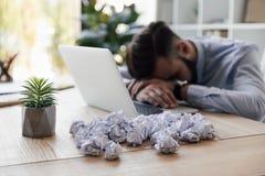 Ύπνος επιχειρηματιών στον εργασιακό χώρο με τα τσαλακωμένα έγγραφα και το lap-top σε το Στοκ Εικόνες
