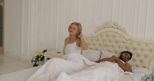 Ύπνος ζεύγους που βρίσκεται κρεβατοκάμαρα γυναικών αγκαλιάσματος ανδρών χαμόγελου πρωινού κρεβατιών εγχώρια άσπρη στη ξυπνήστε ευ απόθεμα βίντεο
