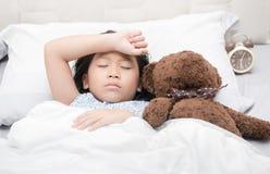 Ύπνος και άρρωστοι κοριτσιών παιδιών στο κρεβάτι με την κούκλα αρκούδων Στοκ Φωτογραφίες