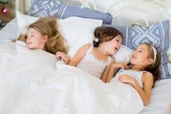 Ύπνος κοριτσιών παιδιών στο κρεβάτι τους το πρωί Χριστουγέννων Στοκ εικόνα με δικαίωμα ελεύθερης χρήσης