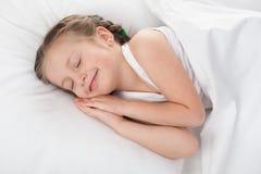 Ύπνος κοριτσιών στο άσπρο κρεβάτι Στοκ εικόνες με δικαίωμα ελεύθερης χρήσης