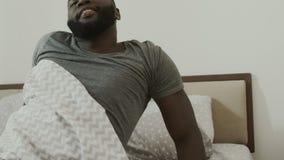 Ύπνος μαύρων στο κρεβάτι Νέο αρσενικό πρόσωπο που ξυπνά στην κρεβατοκάμαρα αργά απόθεμα βίντεο