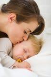 ύπνος μητέρων φιλήματος κινηματογραφήσεων σε πρώτο πλάνο μωρών Στοκ Εικόνες