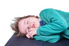 Ύπνος μικρών παιδιών με τα χέρια κάτω από το κεφάλι που απομονώνεται στο άσπρο υπόβαθρο Στοκ φωτογραφία με δικαίωμα ελεύθερης χρήσης