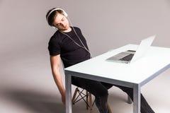 Ύπνος νεαρών άνδρων φορώντας τα ακουστικά και την εργασία για το lap-top στον πίνακα γραφείων του στο άσπρο υπόβαθρο εργασία Στοκ Εικόνες