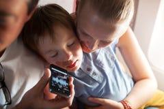 Ύπνος παιδιών με τη μουσική στο τηλέφωνο κυττάρων στο αεροπλάνο Στοκ Φωτογραφίες