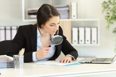 Ύποπτος ανώτερος υπάλληλος που αναλύει σχολαστικά ένα έγγραφο Στοκ εικόνες με δικαίωμα ελεύθερης χρήσης