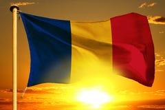 Ύφανση σημαιών της Ρουμανίας στο όμορφο πορτοκαλί ηλιοβασίλεμα με το υπόβαθρο σύννεφων στοκ εικόνες