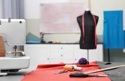 Ύφασμα και ράβοντας εργαλεία στον πίνακα στο ράφτη Στοκ Φωτογραφίες