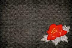 Ύφασμα με ένα κόκκινο λουλούδι Στοκ φωτογραφία με δικαίωμα ελεύθερης χρήσης
