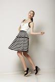 Ύφος μόδας. Ευτυχής νέα ριγωτή γκρίζα φούστα αγοραστών αντίθετα. Μετακίνηση στοκ εικόνα