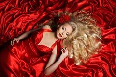 Ύφος τρίχας γυναικών, πρότυπη μακριά σγουρή τρίχα μόδας, κόκκινο ύφασμα κοριτσιών Στοκ Εικόνες