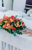 Ύφος φθινοπώρου γαμήλιου συμποσίου Η σύνθεση κόκκινος, πορτοκαλής, κίτρινος, και πράσινος, στεμένος σε έναν άσπρο πίνακα στον τομ στοκ εικόνα