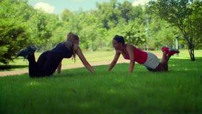 Ώθηση επάνω στην άσκηση Γυναίκες ικανότητας που κάνουν την άσκηση ώθησης UPS υπαίθρια απόθεμα βίντεο