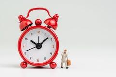 Ώρες απασχόλησης, χρόνος να πάει να εργαστεί ή έννοια προγράμματος συνεδρίασης, μικροσκοπικός επιχειρηματίας αριθμού που εξετάζει στοκ εικόνες