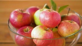 Ώριμα μήλα στο κύπελλο γυαλιού στον ξύλινο πίνακα απόθεμα βίντεο