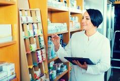 Ώριμα μετρώντας αγαθά γυναικών στο φαρμακείο στοκ φωτογραφία με δικαίωμα ελεύθερης χρήσης