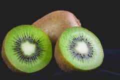 Ώριμα ολόκληρα φρούτα ακτινίδιων και μισά φρούτα ακτινίδιων Στοκ εικόνες με δικαίωμα ελεύθερης χρήσης