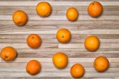 Ώριμα πορτοκάλια σε μια ξύλινη επιφάνεια φιαγμένη από μικρές δρύινες σανίδες Στοκ Εικόνες