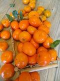 Ώριμα πορτοκαλιά μανταρίνια σε έναν ξύλινο δίσκο στον πίνακα στοκ εικόνες