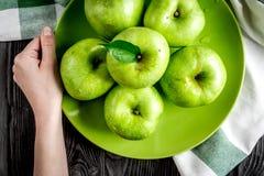 Ώριμα πράσινα μήλα πιάτων στο σκοτεινό ξύλινο διάστημα άποψης επιτραπέζιου υποβάθρου τοπ για το κείμενο Στοκ εικόνα με δικαίωμα ελεύθερης χρήσης