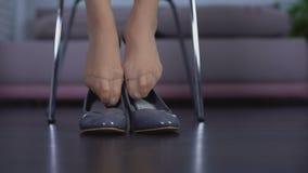 Ώριμα πόδια γυναικών που προσπαθούν στο ζευγάρι των νέων λαμπρών παπουτσιών στο κατάστημα, αγορά μόδας απόθεμα βίντεο